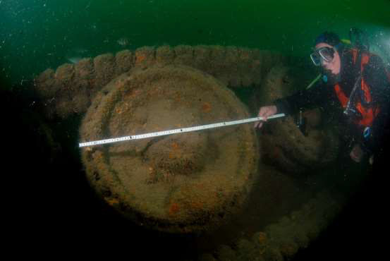 A diver measures one of the Tank road wheels